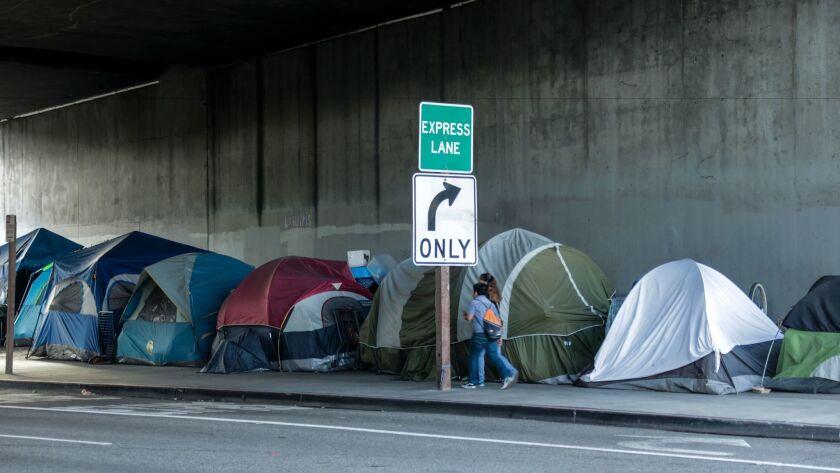 Pedestrians walk past a homeless encampment along 39th Street underneath the 110 Freeway.