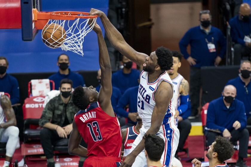 Philadelphia 76ers center Joel Embiid, right, dunks the ball on Washington Wizards center Thomas Bryant, left, during the first half of an NBA basketball game, Wednesday, Jan. 6, 2021, in Philadelphia. (AP Photo/Chris Szagola)
