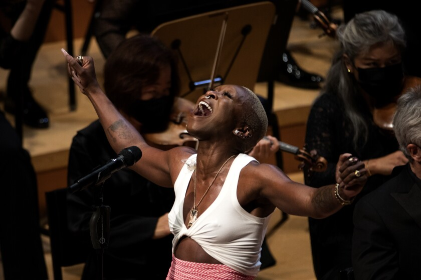 Una mujer al micrófono canta mientras levanta los brazos y la cabeza y cierra los ojos.