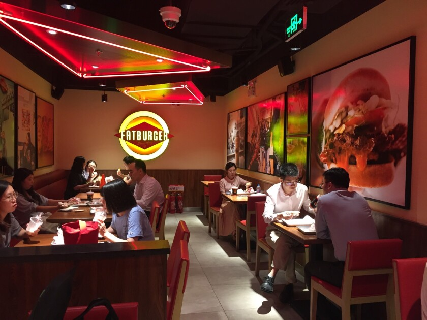 Diners try salmon burgers and the XXXL at Fatburger deep in the basement of the Asian Infrastructure