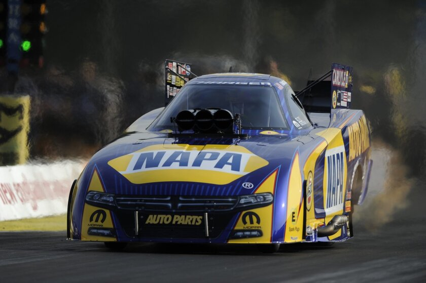 In this photo submitted by the NHRA, Funny Car racer Ron Capps races to the qualifying lead at the NHRA New England Nationals with a run of 3.865 seconds at 325.92 mph. His elapsed time is the second quickest Funny Car pass in NHRA history and a track record at New England Dragway located an hour o