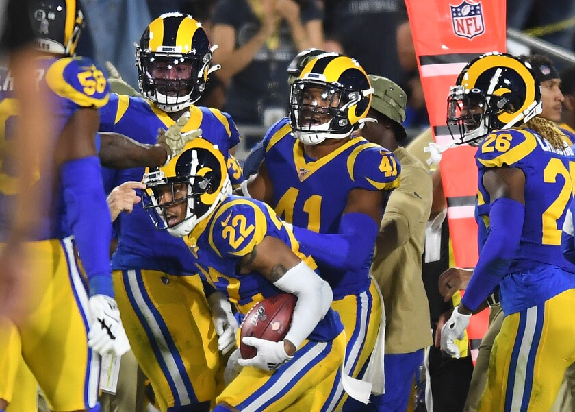 Rams cornerback Troy Hill (22) celebrates his interception with teammates during the second quarter of their game against the Bears on Sunday.
