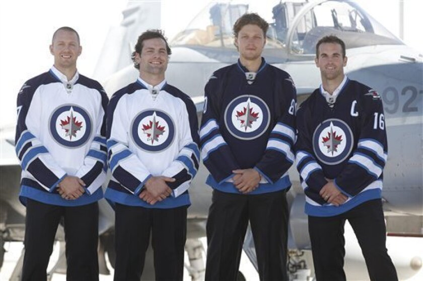 Winnipeg Jets hockey players, from left, Eric Fehr, Mark Stuart, Nik Antropov and Andrew Ladd poses for a photo during a news conference unveiling the team's new jerseys at a Canada Forces base in Winnipeg, Manitoba, Tuesday, Spt. 6, 2011. (AP Photo/The Canadian Press, John Woods)