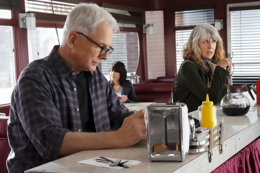 "Mark Harmon and Pam Dawber sitting at a diner counter in ""NCIS"" on CBS."