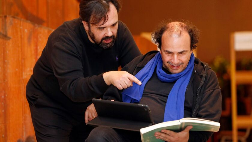 """Italian baritone Roberto de Candia, left, goes over the score with director  Olivier Tambosi at rehearsals earlier this month for Verdi's """"Falstaff"""" at San Diego Opera."""