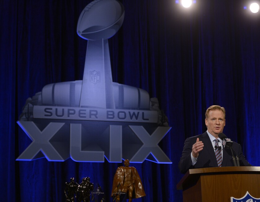 NFL Commissioner Roger Goodell speaks at an NFL podium during a news conference before Super Bowl XLIX in Phoenix.