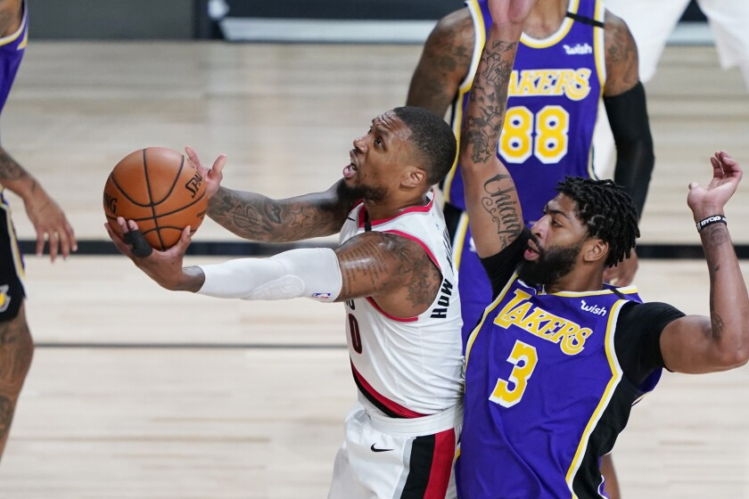 Trail Blazers guard Damian Lillard drives to the basket against Lakers forward Anthony Davis.