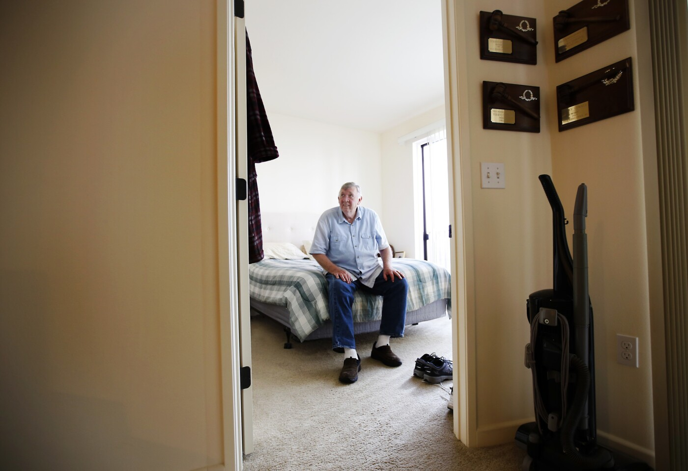 Resident Terry Conner, 73, sits on his bed, putting on his shoes in his apartment at The Woods at Playa.