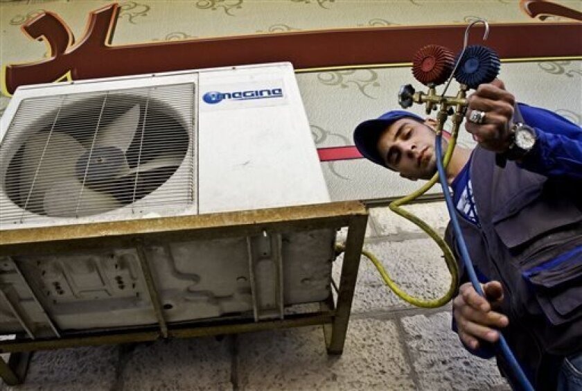 Mohammed Nabouti, a 21-year-old technician, fixes the air conditioner of a shop in Amman, Jordan on Monday, March 4, 2013. Just six months of learning to fix air conditioners changed Nabouti's life. Instead of drifting after high school like many of his jobless friends, Nabouti has taken a small loan to start his own business and recently got engaged. Nabouti's story points to a quick fix the unemployment-stricken Middle East might try until deeper economic reforms can kick in, experts say. This