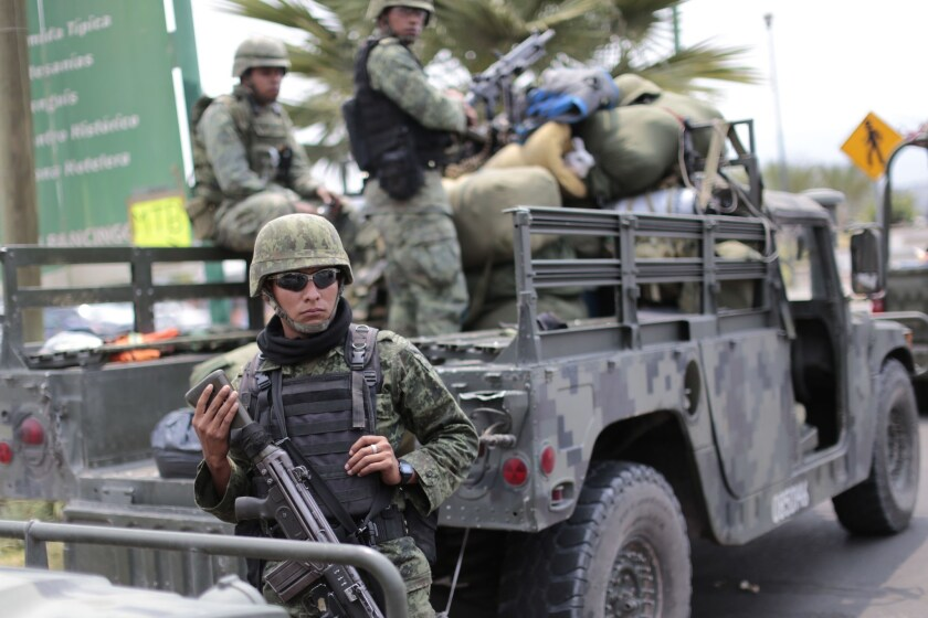 Mexican soldiers stand guard outside Chilapa in the state of Guerrero, a combat zone for drug gangs, in May 2015.