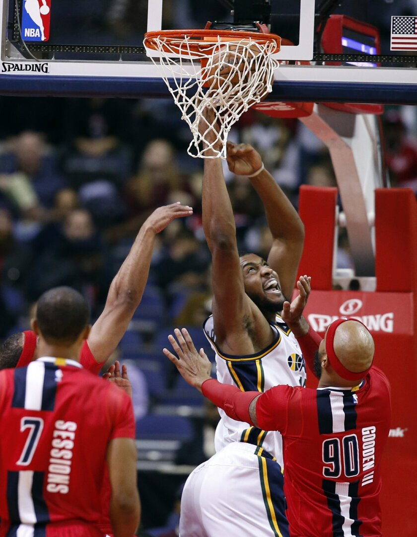 Utah Jazz forward Derrick Favors tries to shoot in front of Washington Wizards forward Drew Gooden (90) during the first half of an NBA basketball game Thursday, Feb. 18, 2016, in Washington. (AP Photo/Alex Brandon)