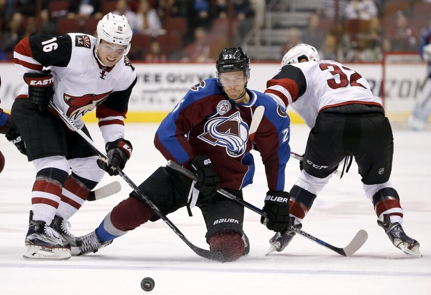 Arizona Coyotes' Max Domi (16) and Tyler Gaudet (32) force the puck away from Colorado Avalanche's Mikhail Grigorenko (25), of Russia, during the first period of an NHL hockey game Thursday, Nov. 5, 2015, in Glendale, Ariz. (AP Photo/Ross D. Franklin)