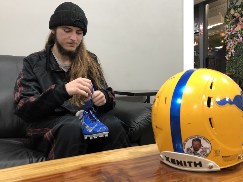 Gabe Murphy ties the laces on one of his football cleats, and a helmet on the table has a sticker of his late father