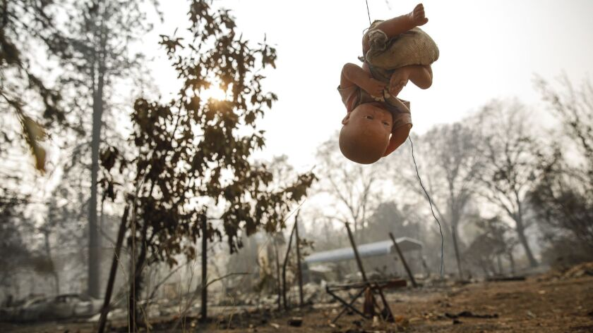 A doll hangs from a string in the backyard of a home that was burned down by the Camp Fire in Paradise, Calif.