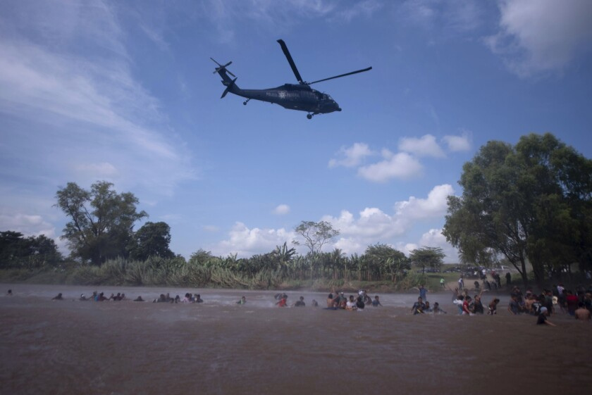 A Mexican federal police helicopter flies close to the Suchiate River, between Mexico and Guatemala, in order to create a downwash force to discourage a new group of Central American migrants bound for the U.S border.