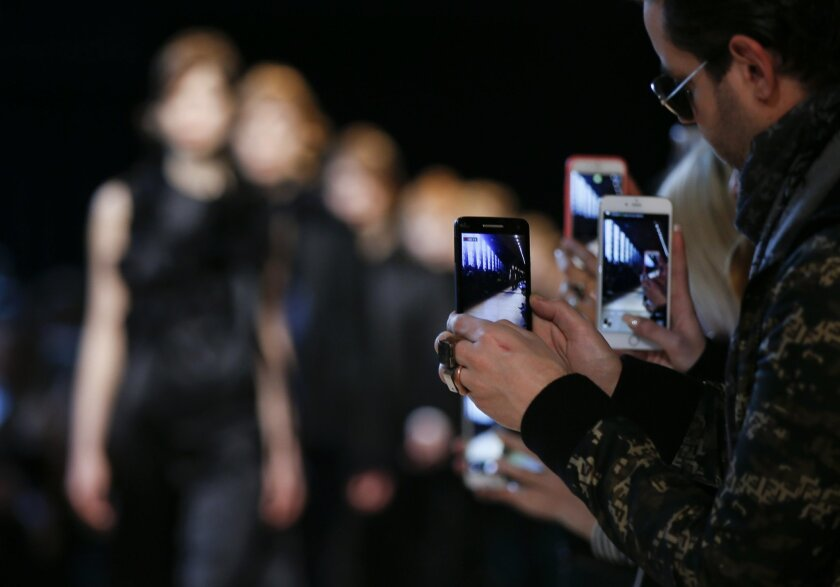 Guests film models with their smart phones during the Costume National women's Fall-Winter 2016-2017 collection, part of the Milan Fashion Week, unveiled in Milan, Italy, Thursday, Feb. 25, 2016. (AP Photo/Luca Bruno)