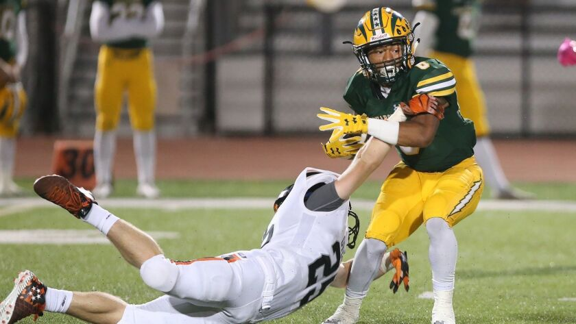 Edison's Isaiah Palmer eludes a tackle by Jake Graham during Sunset League football against Huntingt