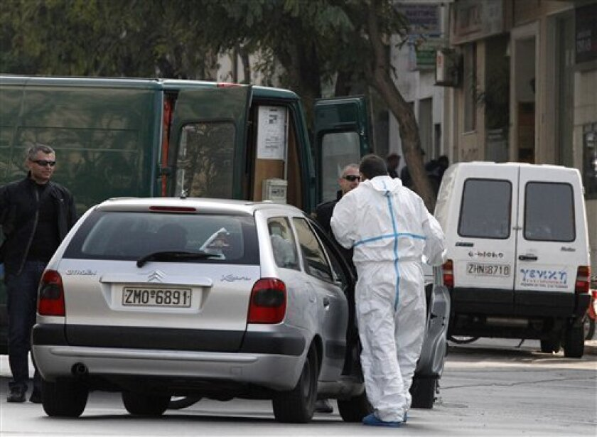 Police stand outside a private delivery company after a controlled blast in Athens, Tuesday, Nov. 2, 2010. Greek police say small parcel bombs exploded at the Swiss and Russian embassies in Athens, and suspicious packages were detonated outside Parliament, the Bulgarian embassy and a courier company. (AP Photo/Dimitri Messsinis)