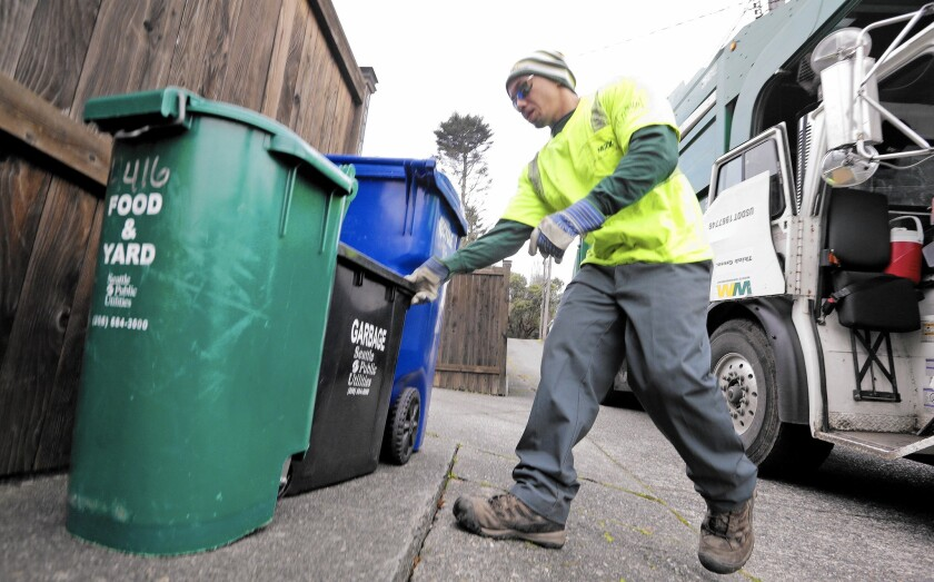 Trash bins in Seattle are checked for proper separation of recyclables.