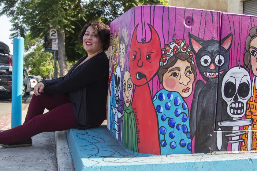 Artist Yvette Roman sits next to her art, a painting of various puppet faces on a utility box in Sherman Heights