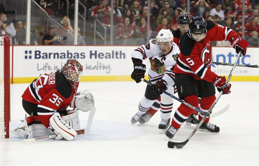 Chicago Blackhawks center Jonathan Toews, center, competes for the puck against New Jersey Devils defenseman Adam Larsson (5) during the first period of an NHL hockey game Friday, Nov. 6, 2015, in Newark, N.J. Devils goalie Cory Schneider is at left. (AP Photo/Julio Cortez)