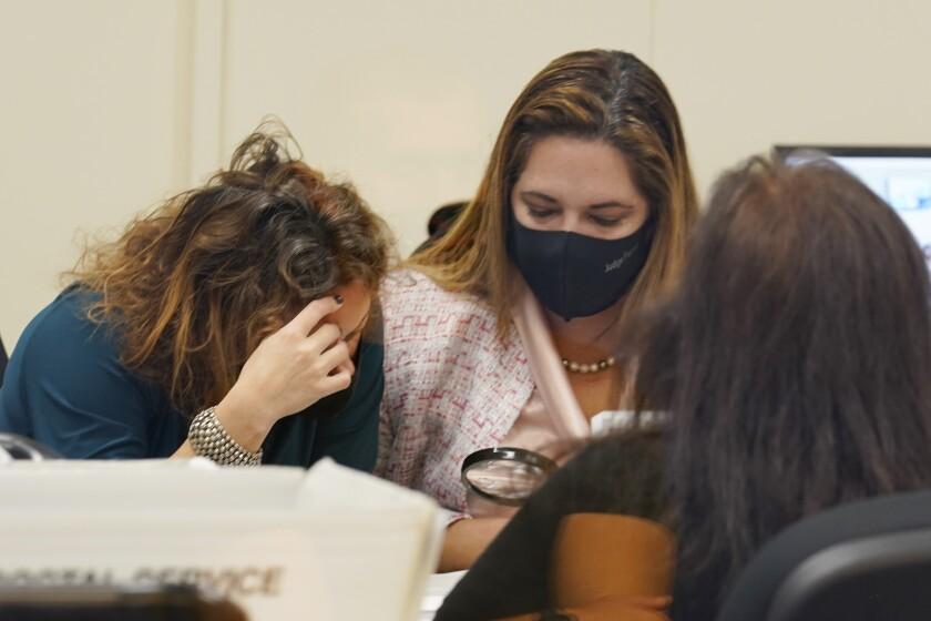 Judges Milena Abreu, left, and Victoria Ferrer examine a vote-by-mail ballot.