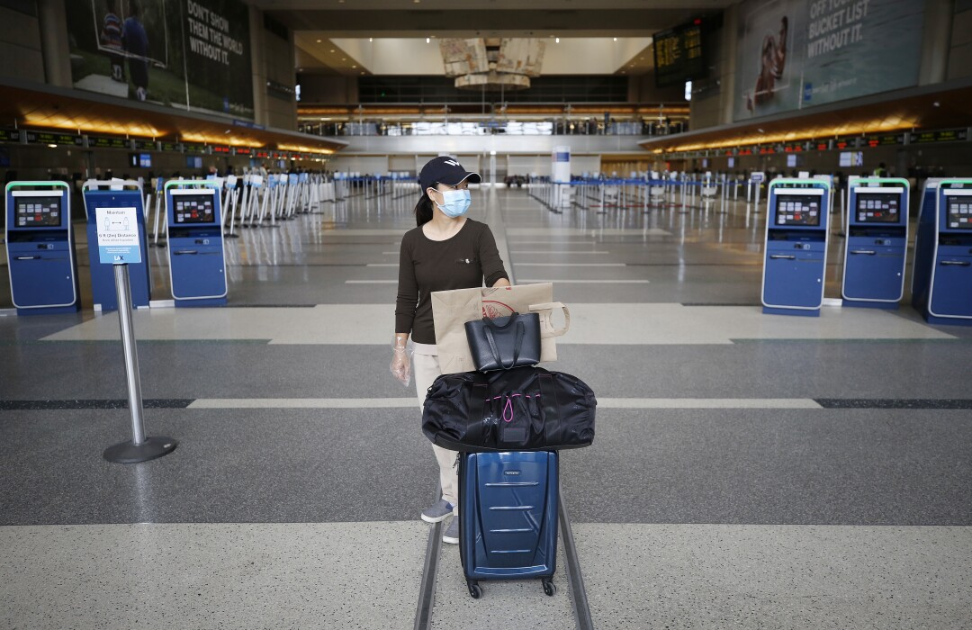 A woman in a face mask at Tom Bradley International Terminal at LAX in early May.