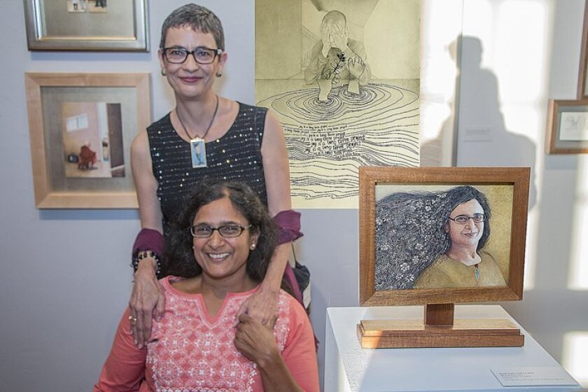 Marianela de la Hoz and Bhavna Mehta, with Marianela's portrait of Bhavna, which she gave her as a gift. Behind them is one of their two collaborative pieces, 'Joy is a long-term project.'