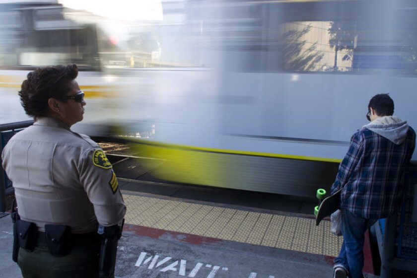 A Los Angeles County sheriff's deputy monitors pedestrians Monday to make sure they don't get near the tracks when trains are approaching.