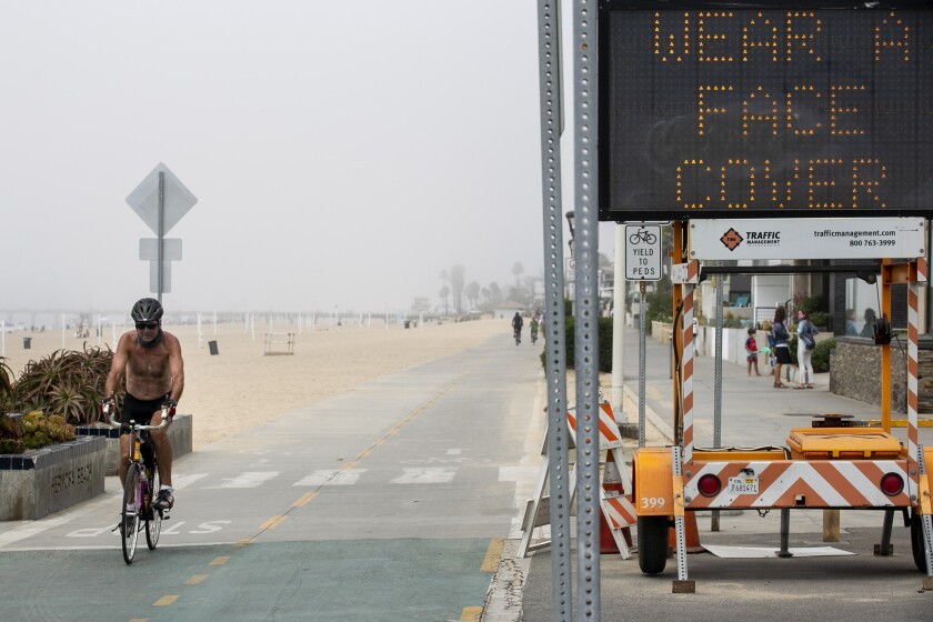 A cyclist passes a sign advising beachgoers to wear masks in Hermosa Beach in September.