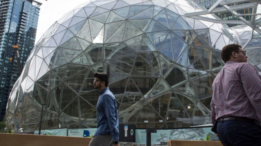 People walk past the signature glass spheres under construction at the Amazon corporate headquarters in Seattle. The online giant will decide next year which metropolitan area will be the site of its second headquarters.