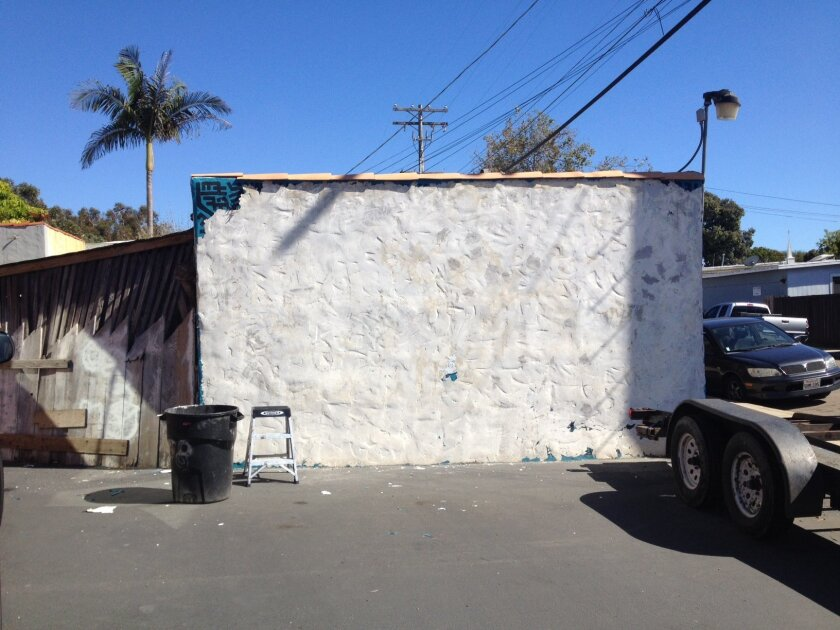 The bare north wall behind Leucadia Glass after being stripped of the acrylic paint that made up the second distinctive mural by Bleu Avina.