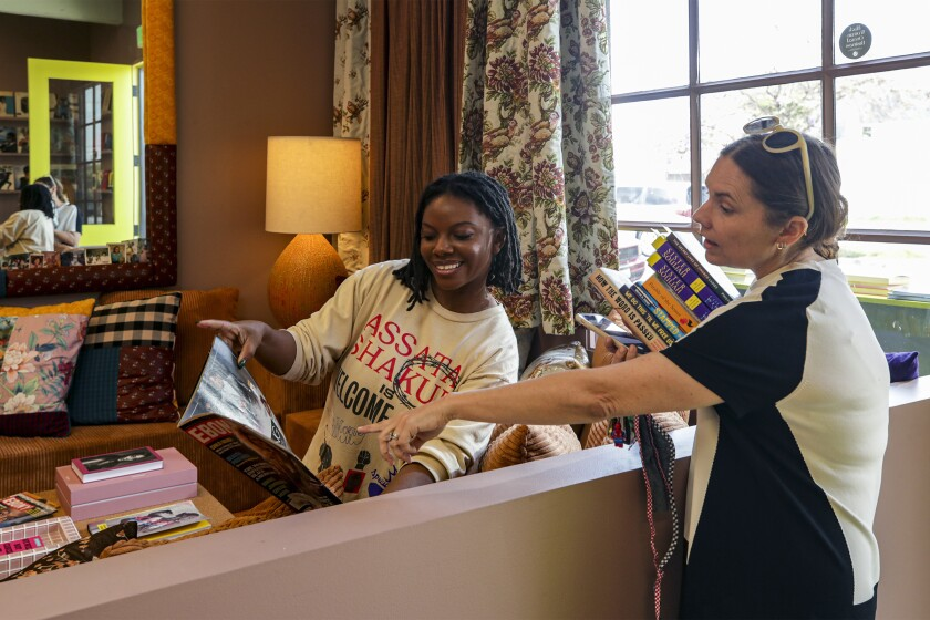 A woman holds an Ebony magazine while a second woman points to a photo.