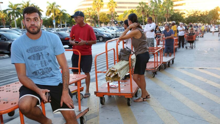 Max Garcia of Miami waits in line, where he has been since dawn, to purchase plywood at a Home Depot