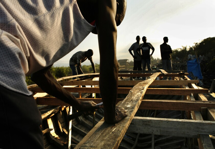 A Haitian man works in 2010 on building a boat he hopes to use to get to the United States.