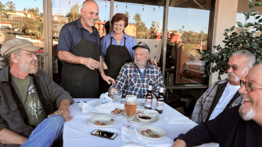 In front of Felliccia's Italian Restaurant and Deli owner Sam Feliccia and his sister, 30 year employee Cathy Parisi, chat with friends that have been coming there for many years, seated LtoR: Dwain Knapp, Ken Burris, Lenny Odell and Larry Kalmes. Sam an