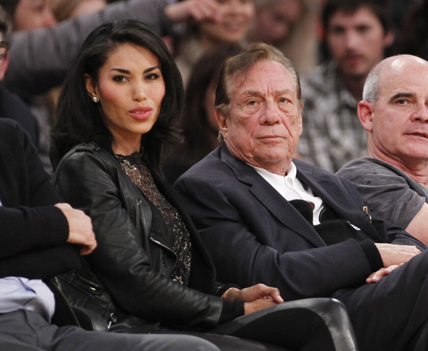 Los Angeles Clippers owner Donald Sterling, right, and V. Stiviano watch the Clippers play the Los Angeles Lakers during an NBA preseason basketball game in Los Angeles in 2010.