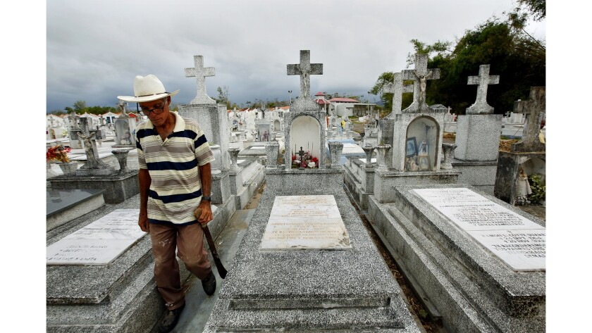 Heriberto Riveiro, 41, passes the grave of Hermenegildo Cotte Melendez, who died because there was no electricity for his oxygen tank during Hurricane Maria.(Carolyn Cole / Los Angeles Times)