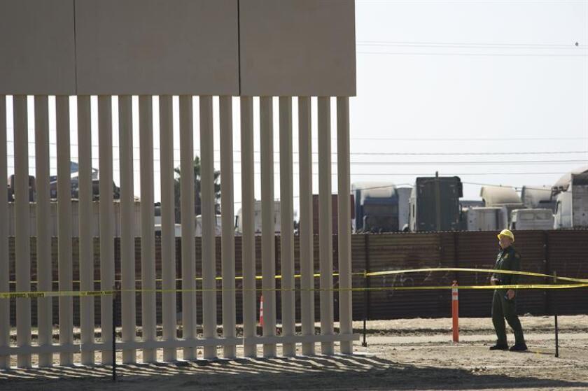 Un agente de la Patrulla Fronteriza observa las labores de construcción de uno de los prototipos del muro fronterizo. EFE/Archivo
