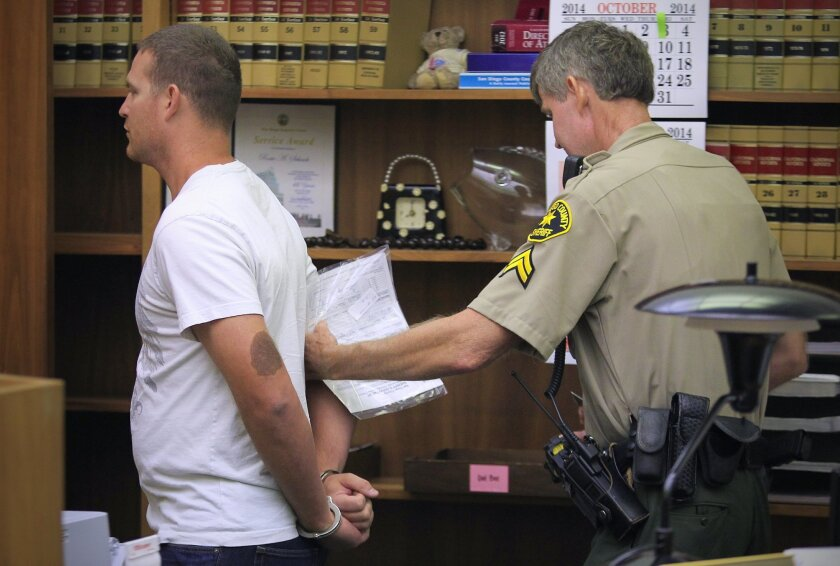 Former San Diego police officer Christopher Hays is led away in handcuffs by San Diego County Sheriff's Deputy Robert Townsend after surrendering in the San Diego Superior Courtroom of Judge Charles Rogers. Hays will spend one year in county jail after pleading guilty for sexual misconduct charges while a police officer.