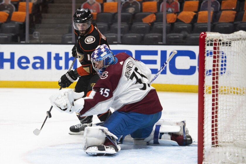 Ducks center Adam Henrique tries to deflect the puck in front of Colorado Avalanche goaltender Jonas Johansson.