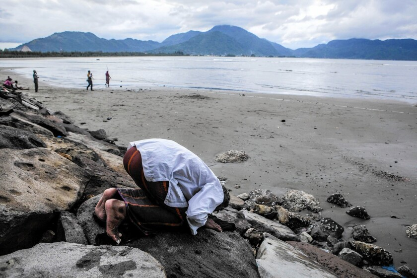 A fisherman prays on the beach in Banda Aceh, Indonesia.