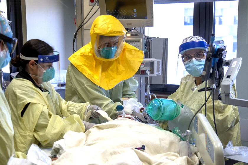 A medical team in face shields, masks and other protective gear treats a patient on a hospital bed.