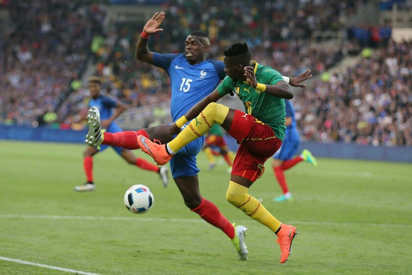Cameroon's Ambroise Oyongo Bitolo, right, challenges for the ball with France's Paul Pogba during a friendly soccer match between France and Cameroon at the La Beaujoire Stadium in Nantes, western France, Monday, May 30, 2016. The French squad is in preparation for the EURO 2016 soccer championship