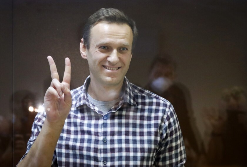 FILE - In this Saturday, Feb. 20, 2021 file photo, Russian opposition leader Alexei Navalny gestures as he stands in a cage in the Babuskinsky District Court in Moscow, Russia. Navalny, whom many regarded as a top candidate for the Nobel Peace Prize, is on Monday, Oct. 11 congratulating countryman Dmitry Muratov for winning it. Muratov, editor of the independent newspaper Novaya Gazeta, was named prize co-laureate last week along with investigative journalist Maria Ressa of the Philippines. (AP Photo/Alexander Zemlianichenko, file)