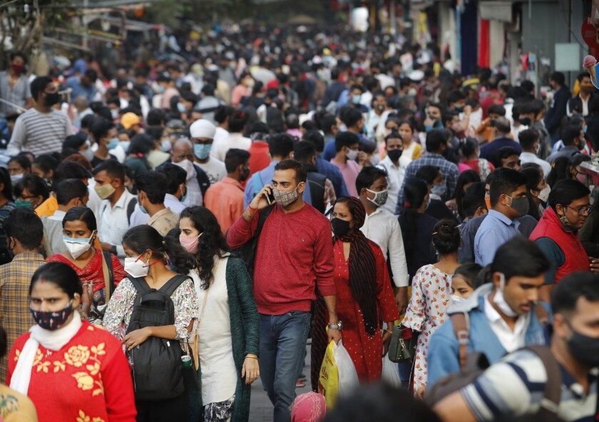 People throng a market to shop ahead of the Diwalli festival in New Delhi, India, Thursday, Nov. 12, 2020. Authorities in New Delhi have banned firecrackers and are appealing to people to celebrate the Hindu festival of lights at home. Coronavirus infections have been rising in the capital and authorities are worried large festival crowds will worsen the virus situation.(AP Photo/Manish Swarup)
