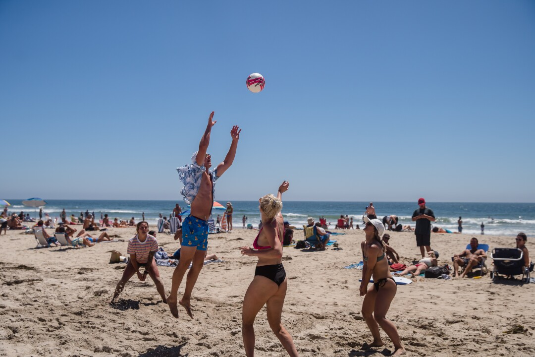 People play with a volleyball on the beach on July 5, in Pacific Beach