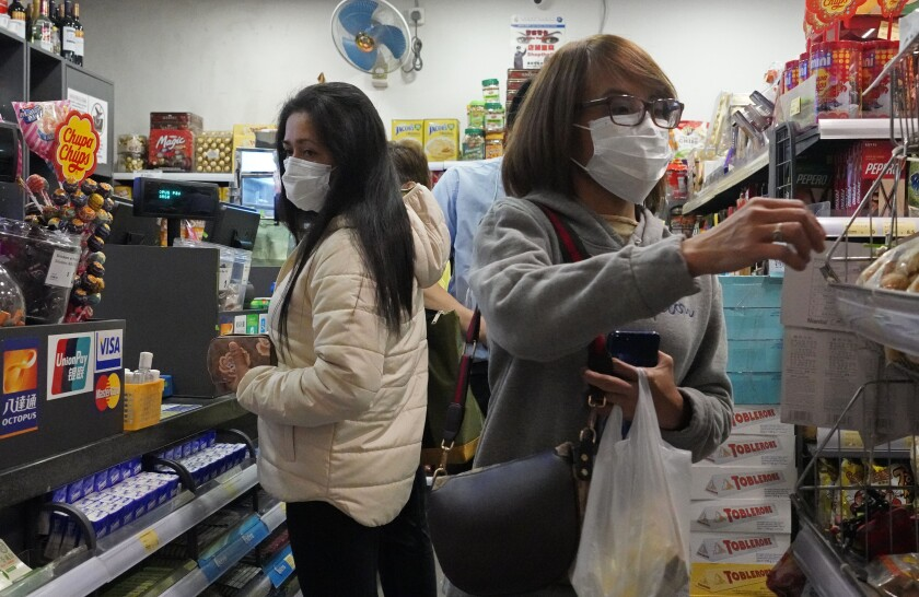 People wear protective face masks as they make purchases from a convenience store in Hong Kong, Monday, Feb, 3, 2020. Hong Kong leader Carrie Lam in a Monday press conference says the city will shut almost all land and sea border control points to the mainland from midnight to stem the spread of the novel coronavirus from China. (AP Photo/Vincent Yu)