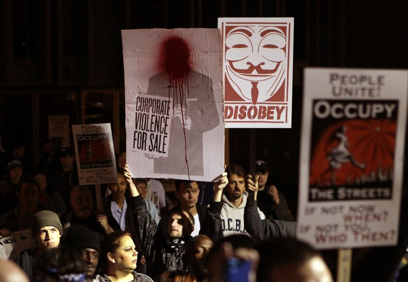 Protesters hold signs at Friday night's Occupy San Diego rally.