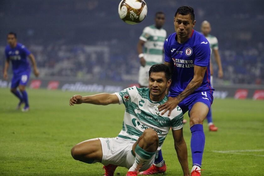 Santos Laguna's Eduardo Aguirre, bottom, and Cruz Azul's Julio Dominguez compete for the ball